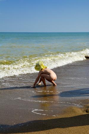 Enfant nu sur la plage de mer jouant au sable et aux vagues Banque d'images - 82997922