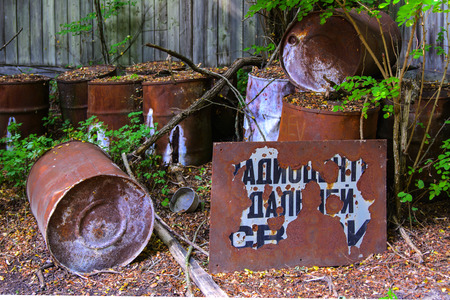 Old rusty barrels with radiation. Dead military unit. Consequences of the Chernobyl nuclear disaster, August 2017.