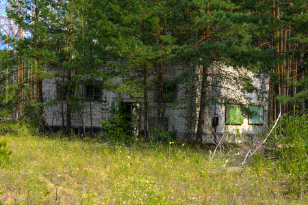 An old abandoned garage for repairing vehicles in the zone. Dead military unit. Consequences of the Chernobyl nuclear disaster, August 2017.