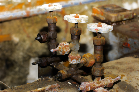 Old and rusty shut-off valve and taps from equipment at an abandoned and destroyed factory amid chaos. Destruction and vandalism. Ukraine.
