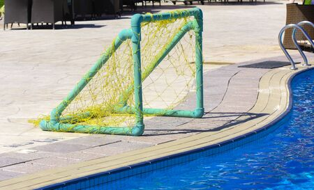 The gate with a grid for playing water polo with a ball on the edge of the pool with clear blue water. Stock Photo