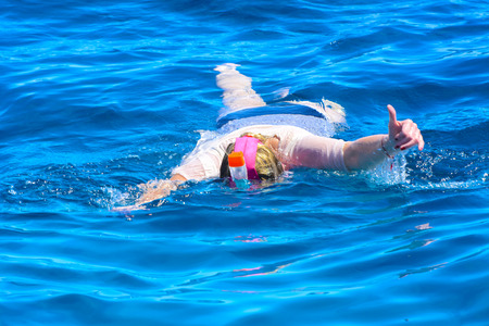 Tourists swim in the transparent turquoise sea and see beautiful colorful fish on the background of corals in the Red Sea. Relaxation during rest. Egypt.
