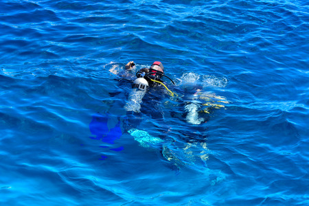 Divers on the clear and turquoise Red Sea on immersion in beautiful corals and colorful fish. The teacher teaches the student the rules of immersion in water. Summer, vacation. Egypt