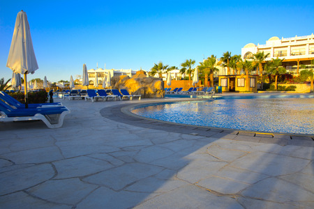 Sharm el-Sheikh, Egypt - March 14, 2018.  Beautiful pool in Cyrene Grand Hotel with clear blue water on the background of the sea, blue sky and green palm trees. Beach chaise longue.