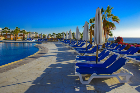 Sharm el-Sheikh, ?????? - 14 ????? 2018 ????. Beautiful pool in Cyrene Grand Hotel with clear blue water on the background of the sea, blue sky and green palm trees. Beach chaise longue.