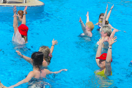 Sharm el-Sheikh, Egypt - March 14, 2018. The fitness concept, a fitness class, a group of people is engaged in aqua aerobics in the pool on a summer day outdoors. Accommodation in Cyrene Grand Hotel