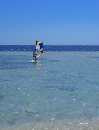 A girl runs a board with a sail on the mast due to the inclination and turn of the mast. Windsurfing. The concept of summer vacations, recreation and travel. Standard-Bild