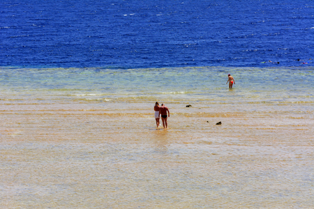 People walk along the shallow Red Sea in the coastal strip. The concept of summer vacations, recreation and travel. Фото со стока