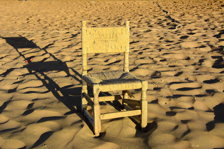 An old wicker chair from the vine is thrown out on an empty seashore against a background of yellow sand. Abandoned, unnecessary things. Vacation, tourism.