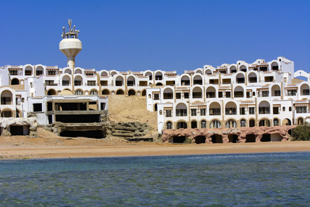 Sharm el-Sheikh, Egypt - March 14, 2018. Fragments of an unfinished construction and abandoned hotel on the Red Sea on a background of yellow sand and blue sky. Travel rest on a summer day outdoors. Reklamní fotografie