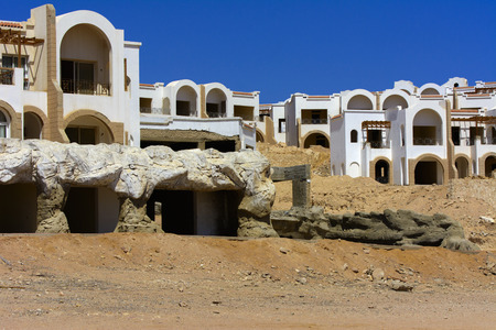 Sharm el-Sheikh, Egypt - March 14, 2018. Fragments of an unfinished construction and abandoned hotel on the Red Sea on a background of yellow sand and blue sky. Travel rest on a summer day outdoors. Archivio Fotografico