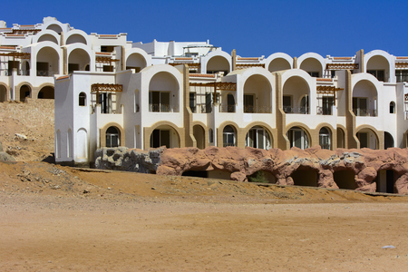 Sharm el-Sheikh, Egypt - March 14, 2018. Fragments of an unfinished construction and abandoned hotel on the Red Sea on a background of yellow sand and blue sky. Travel rest on a summer day outdoors. Reklamní fotografie - 125227860