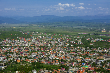Colorful exalted view from a bird's eye view to houses in residentialdistrict in the city of Khust, Western Ukraine with high mountains in the background on a background of green vegetation.