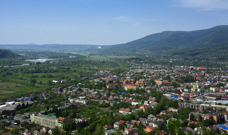 Colorful exalted view from a birds eye view to houses in residential  district in the city of Khust, Western Ukraine with high mountains in the background on a background of green vegetation. Фото со стока
