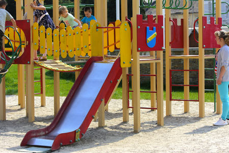 Khust, Ukraine - April 22, 2018. Little children run around and play in the playground. Game center for a young child. Little girl is playing outdoors. The concept of summer children's entertainment.