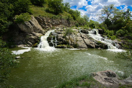 The waterfall on the river flows through and over the rocks covered with lichen and moss against a background of green vegetation and a blue sky. Stok Fotoğraf