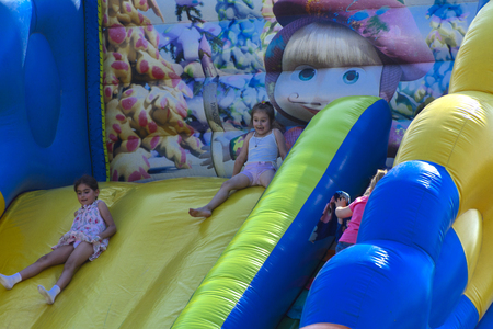 Zarechany, Ukraine - June 10, 2018. Children play on an inflatable carousel. Meeting of residents at the festival of the village of Zarechany. Public events, charity, rural society