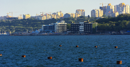 Magnificent panorama, view from the sea to the coastal strip of the city before sunset in the soft sunlight. High-rise buildings and commercial facilities on the shore