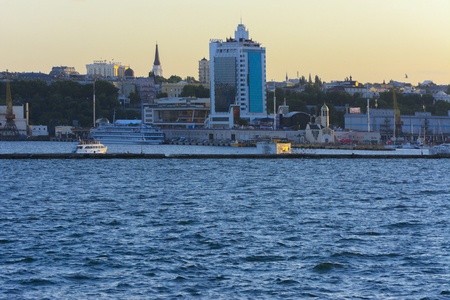 Odessa, Ukraine - August 08, 2018. Magnificent view from the sea on the coastal strip of the city before the sunset in soft light. High-rise buildings and commercial facilities on the shore