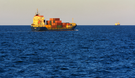 Odessa, Ukraine - August 08, 2018. A large cargo ship transports containers in the open sea in the evening soft sunlight against a blue sky. The concept of freight traffic on the Black Sea, Ukraine. Editoriali