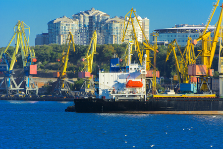 Odessa, Ukraine - August 8, 2018. Big working cranes for loading containerships and various cargoes to the ships at the shipyard against a beautiful evening blue sky in soft colors. Cargo delivery Editoriali