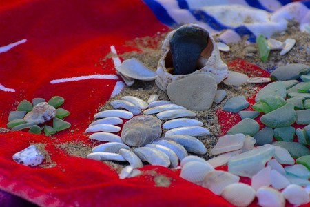 Sea shells - a variety of sea shells from the beach. Shells, sea colored stones on a red towel on the sand. Summer beach background. View from above. Decorative composition is flat.