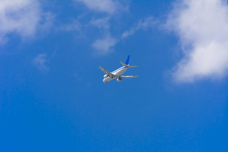 A large passenger airliner is a plane with a big wingspan high in the sky. Transport tourists for exotic holidays against the blue sky and white clouds