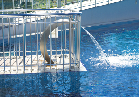 Empty blue water pool with a waterfall stream in action. Relaxation pool, spa hydrotherapy. The concept of hydromassage and relaxation.