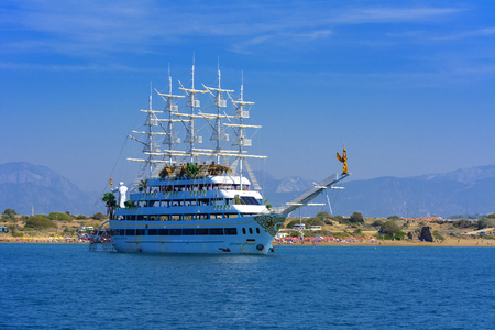 Alanya, Turkey - October 05, 2018. A large white pirate-style sailing ship is moored near the coast against a blue sky. Photos of the ship from the sea. The concept of summer holidays, sports, tourism