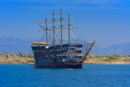 Alanya, Turkey - October 05, 2018. A large dark sailing ship in a pirate style is moored near the shore against a blue sky. Photos of the ship from the sea. The concept of summer holidays, sports, tourism Editorial