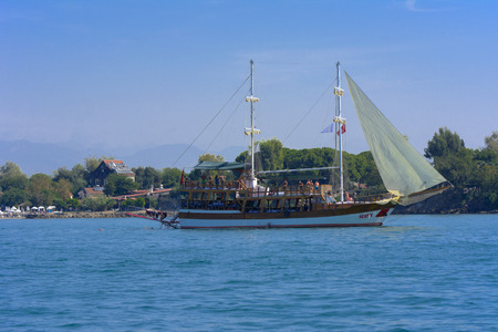 Alanya, Turkey - October 05, 2018. A small sailing ship in a pirate style runs along the coast against a blue sky. Photos of the ship from the sea. The concept of summer holidays, sports, tourism Editoriali