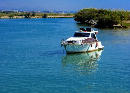 White speedboat on the background of the coast and blue sky. Photos of the ship from the sea. The concept of summer holidays, sports, tourism