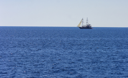 A large sailing ship in a pirate style in the open sea against a blue sky. Photos of the ship from the sea. The concept of summer holidays, sports, tourism