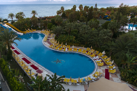 Alanya, Turkey - October 05, 2018. Beautiful pool in Kirman Sidera. Luxury hotel with clear blue water in the pool at night. Beach chaise longue, summer vacation, tourism