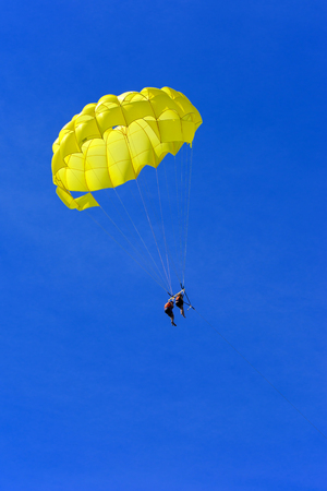 A skydiver flies with a colorful parachute tied to a speedboat on the sea against the backdrop of mountains with a blue sky. The concept of summer holidays, vacation, tourism. Standard-Bild