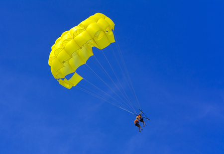 A skydiver flies with a colorful parachute tied to a speedboat on the sea against the backdrop of mountains with a blue sky. The concept of summer holidays, vacation, tourism. Stock Photo