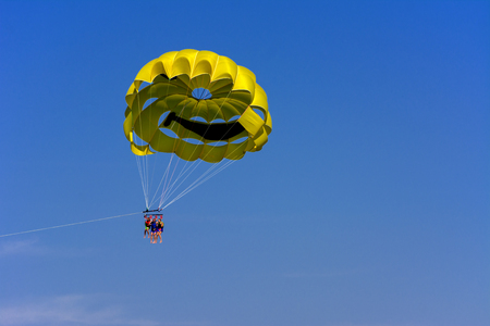 A skydiver flies with a colorful parachute tied to a speedboat on the sea against the backdrop of mountains with a blue sky. The concept of summer holidays, vacation, tourism. Editorial