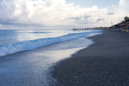 A small wave runs onto the sandy beach in the soft morning rays of the sun. Photos of the coast in the early morning. The concept of summer holidays, sports, tourism