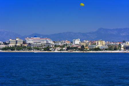 Alanya, Turkey - October 05, 2018. Beautiful hotels of Turkey against the background of distant mountains and blue sky. Photos of coast from the sea. The concept of summer holidays, sports, tourism Reklamní fotografie - 117431706