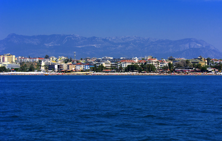 Alanya, Turkey - October 05, 2018. Beautiful hotels of Turkey against the background of distant mountains and blue sky. Photos of coast from the sea. The concept of summer holidays, sports, tourism