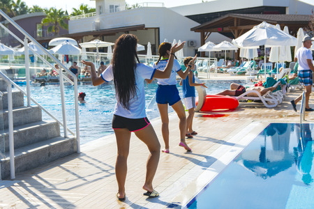Alanya, Turkey - October 05, 2018. Aqua aerobics instructor conducts classes in the blue clear water of the Kirman Sidera Luxury hotel pool. Fitness concept, summer vacation, sport, tourism Sajtókép