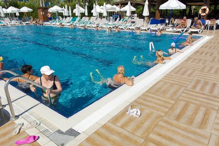 Alanya, Turkey - October 05, 2018. A group of people is engaged in aqua aerobics in the blue clear water of the pool at Kirman Sidera Luxury Spa. Fitness concept, summer vacation, sport, tourism