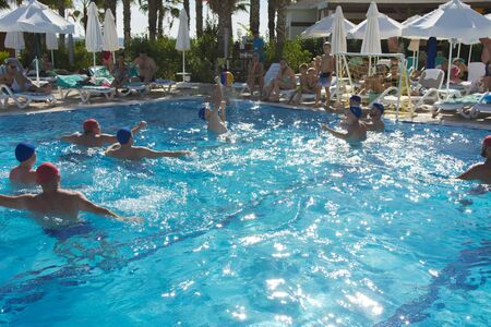 Alanya, Turkey - October 05, 2018. A group of people plays water polo in the blue clear water of the Kirman Sidera Luxury hotel pool. Fitness concept, summer vacation, sport, tourism