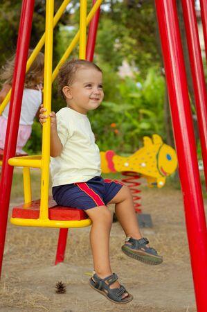 little boy on swings photo