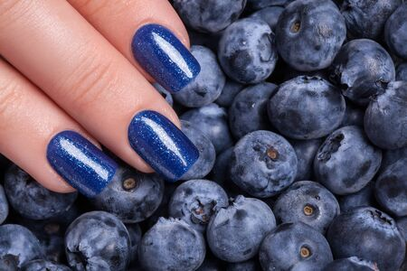 varnish for the nails: Beautiful blue nails on the background of berries. Stock Photo