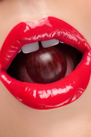 gloss: Lip gloss painted red with cherries in the mouth. Stock Photo