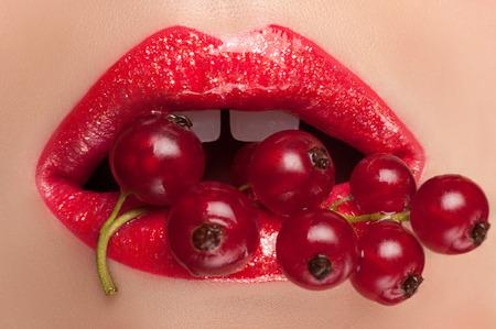 labios rojos: Labios pintados con brillo grosella roja en la boca.