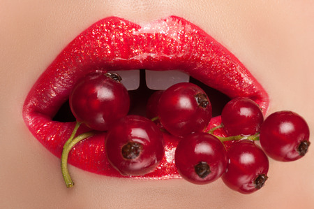 lips: Lips painted with red currant shine in the mouth. Stock Photo