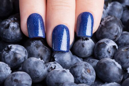 Beautiful blue nails on the background of berries. Stock Photo