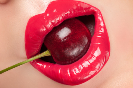 lip gloss: Lip gloss painted red with cherries in the mouth. Stock Photo